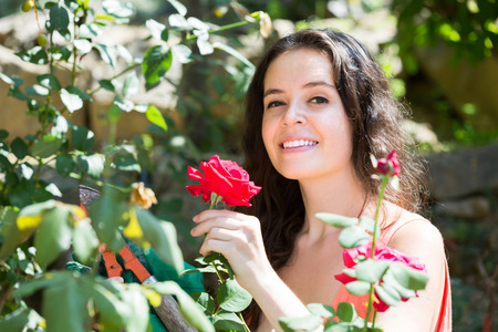 pruning scissors: Smiling long-haired girl working with pruning scissors in the garden