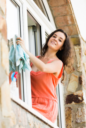 sprayer: cheerful maid cleaning windows with rag and sprayer Stock Photo