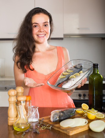 fryingpan: Happy  woman with raw fish on roasting pan at home kitchen Stock Photo