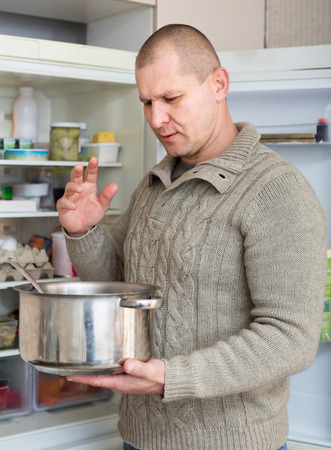 frowy: Man holding his nose because of bad smell from food near refrigerator at home