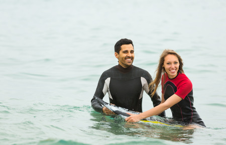 waist deep: Smiling couple swimming in wetsuits with surf board Stock Photo