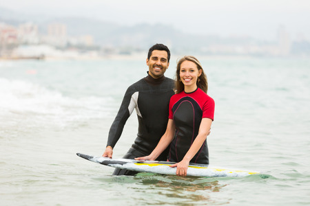waist deep: Smiling active couple swimming in wetsuits with surf board