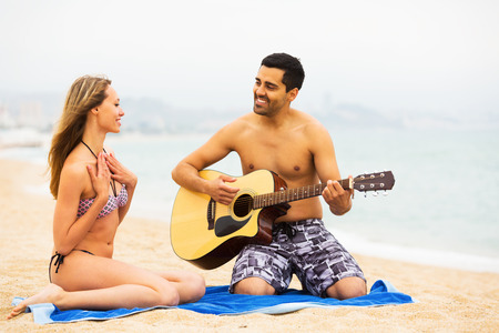 25s: Positive young guy plays guitar for his girlfriend Stock Photo