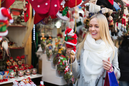 25s: Smiling young  blonde female shopping at festive fair before Xmas Stock Photo