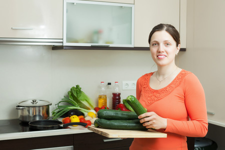 vegetable marrow: positive woman cooking with  vegetable marrow in home kitchen