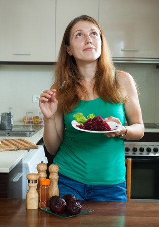 ordinary woman: Casual ordinary woman in green eating boiled beets at home