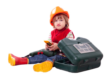 Emotional child in builder hardhat with tools. Isolated over white background photo