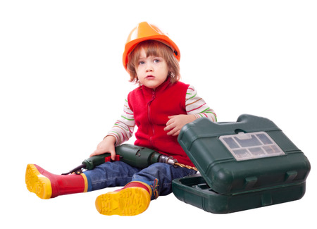 Child in builder hard hat with tools. Isolated over white background photo