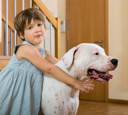 argentino: little girl on the floor with dogo Argentino