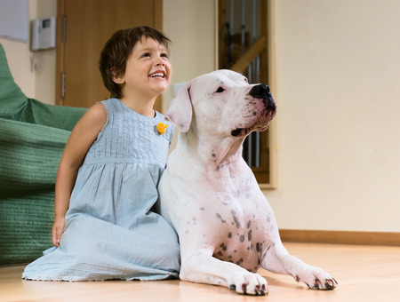 argentino: smiling female toddler on the floor with dogo Argentino