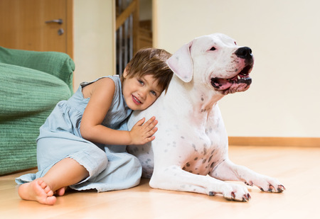 argentino: Pretty girl toddler on the floor with dogo Argentino