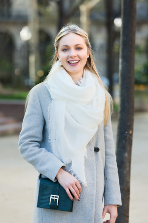 charmingly: Young beautiful blonde standing on a street outdoors smiling charmingly Stock Photo