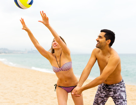adult beach: Positive young couple playing volleyball on the beach. Focus on the man