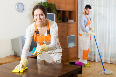 Happy professional cleaners with equipment clean of client house