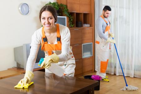 servicio domestico: Limpiadores profesionales felices con el equipo limpio de la casa del cliente Foto de archivo