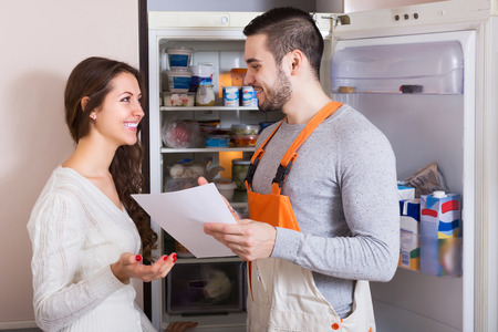 Happy female client and smiling warranty service man near fridge at kitchen