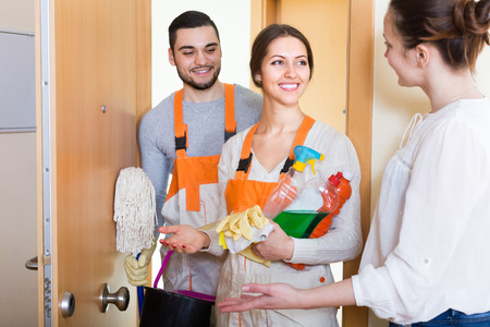 cleaning crew: Happy housewife meeting cleaning crew at apartment doorway. Focus on woman