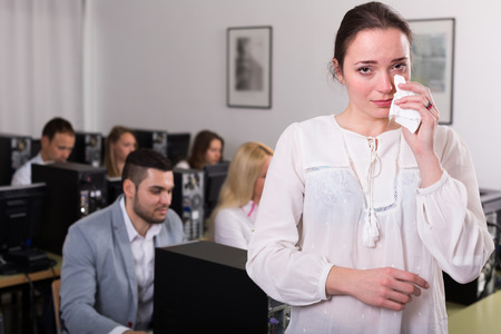 working area: Crying office worker at open space working area Stock Photo