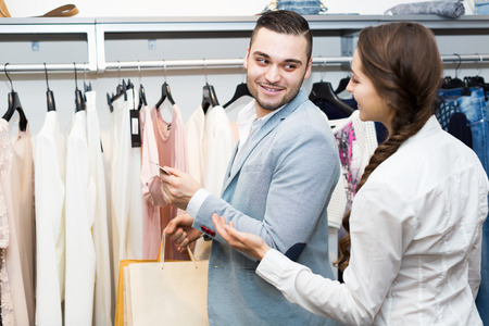 store clerk: Store clerk serving smiling purchaser at fashionable apparel store Stock Photo