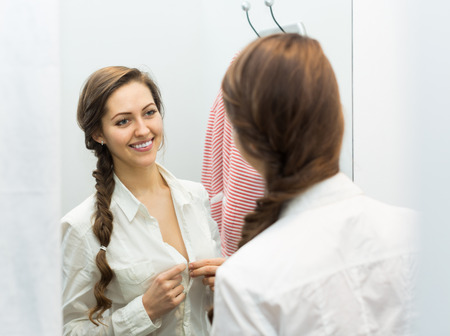 brune: Portrait of happy female with new garment at fitting-room
