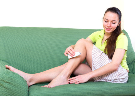 liniment: Woman sitting on a couch indoors and applying medicament gel to her hurt feet