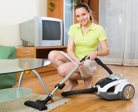 servicio domestico: Mujer joven en la limpieza de la falda en casa con la aspiradora
