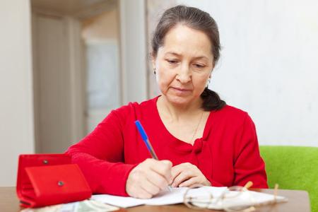 plaintive: Sad mature woman fills utility bills at her home