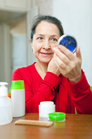corrugation: mature woman stares to facial rhytid on face in mirror Stock Photo