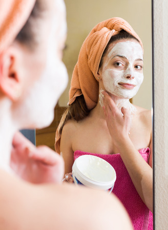 house robe: Girl applying face pack in front of the mirror indoors Stock Photo