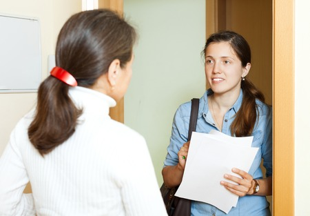 Mature woman answer questions of outreach worker with papers at door in home