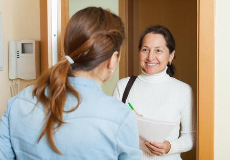 encuestando: Mujer sondeo entre la gente en la puerta en casa