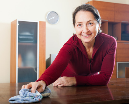 cleanser: Happy smiling woman cleaning table with cleanser and rag at living room Stock Photo