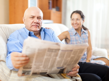 gladful: Portrait of laughing mature woman and elderly man with newspaper