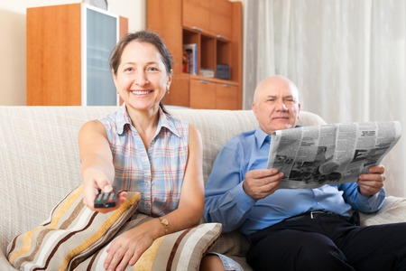 Happy couple grandparents reading a newspaper at home