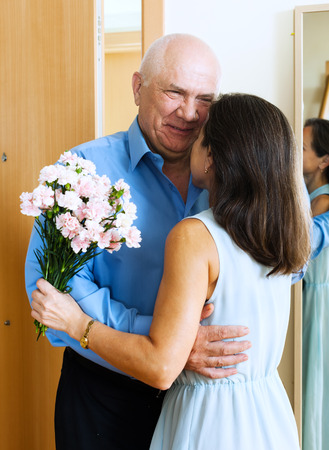 came: Mature man came to woman with bunch of flowers at home