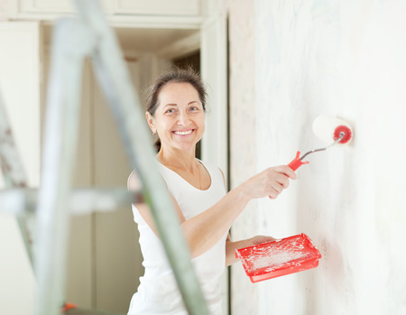 housepainter: Happy mature woman makes repairs at home