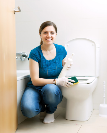 Happy housewife in blue cleaning toilet bowl with sponge in bathroom at home photo