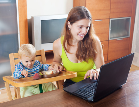 malcontent: Happy young mother working with laptop in home