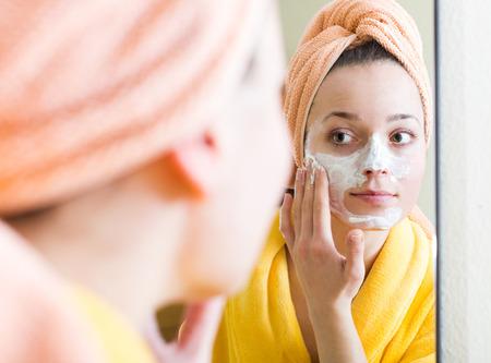 caras felices: Mujer joven en la albornoz que aplica mascarilla interior