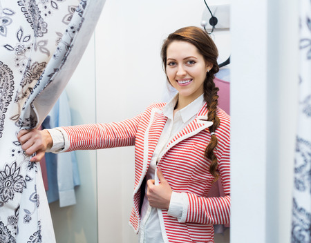 brune: Attractive happy girl trying on new blouse at apparel store Stock Photo