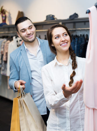 store clerk: Positive store clerk serving happy purchaser at fashionable apparel store Stock Photo