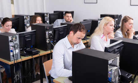 harassing: Bored european staff sitting at desks and looking at PC screens Stock Photo