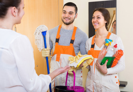 cleaning crew: Smiling housewife meeting cleaning crew with equipment at apartment doorway. Focus on man Stock Photo