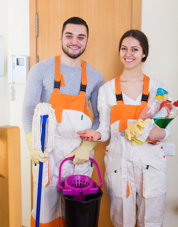 houseman: Professional happy cleaners with equipment standing at doors of client house