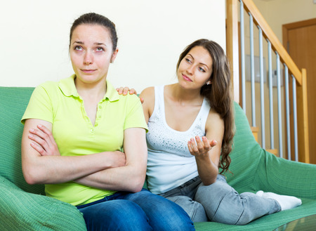 kindred: Cheerful girl supports her friend in a difficult situation. Focus on the left woman Stock Photo