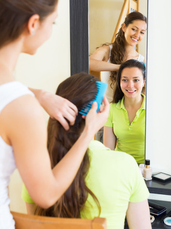 cognate: Smiling young girl combing the hair in front of mirror