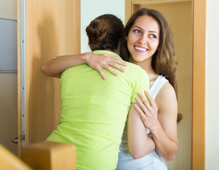 neighbours: Cheerful smiling girl meeting girlfriend at the door
