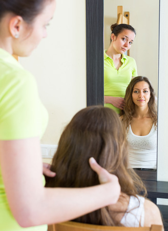 kindred: Young woman brushing her friend in front of the mirror at home