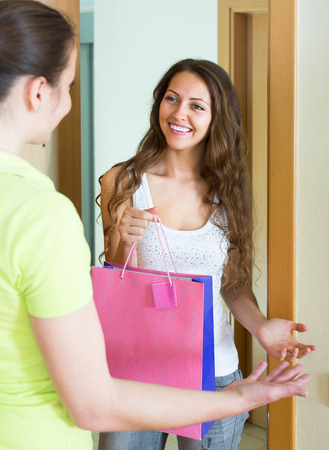 cognate: Young smiling girl visiting her sister with birthday present