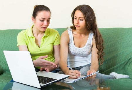 parsimony: Sad women with financial documents and laptop in home interior